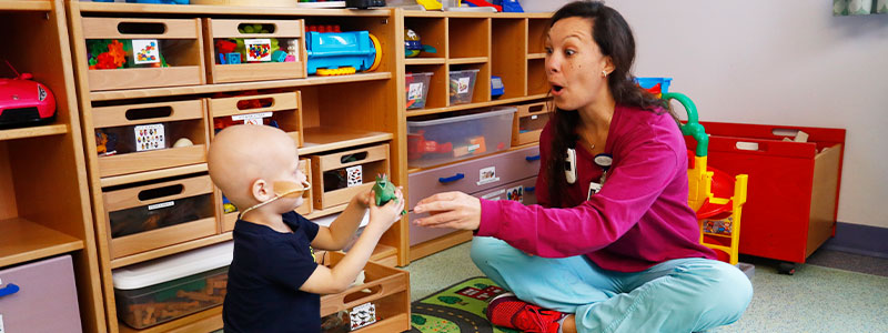 Boy, girl and mom in play area with therapy dog