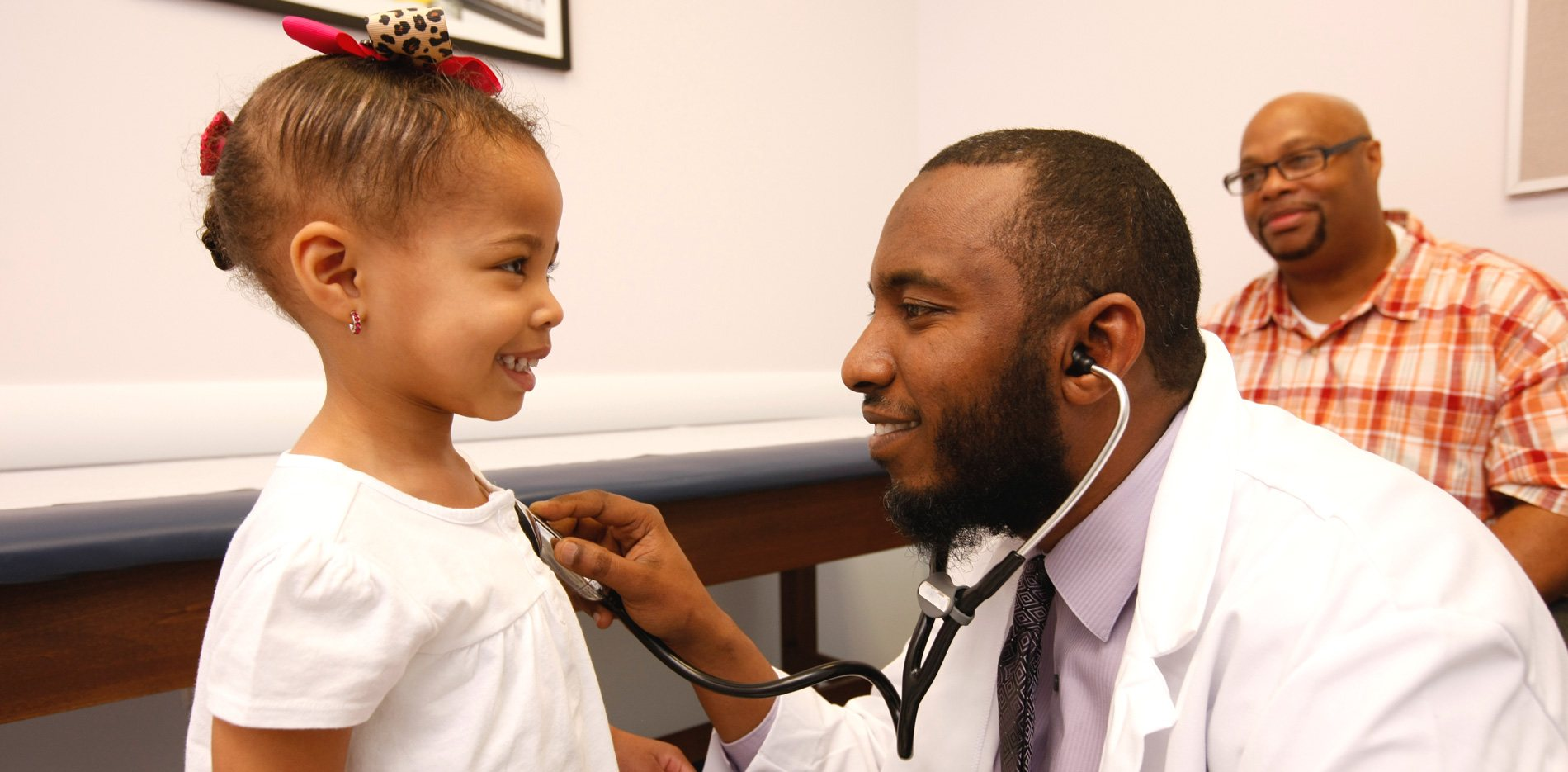 Doctor with young girl and father